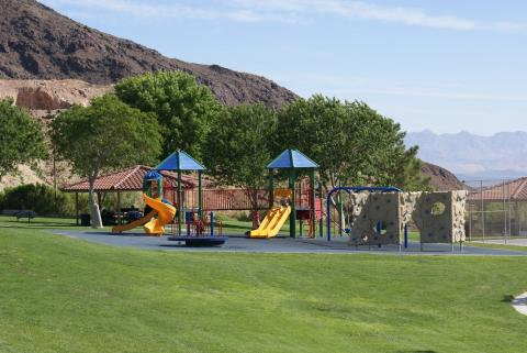 A small playground area with 3 slides sits on a manicured lawn at the beautiful Hemenway Valley Park