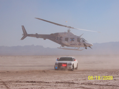 A helicopter landing next to a police cruiser in a desert area